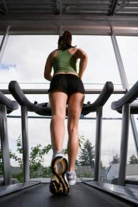 Young Woman Jogging on Treadmill --- Image by © Royalty-Free/Corbis